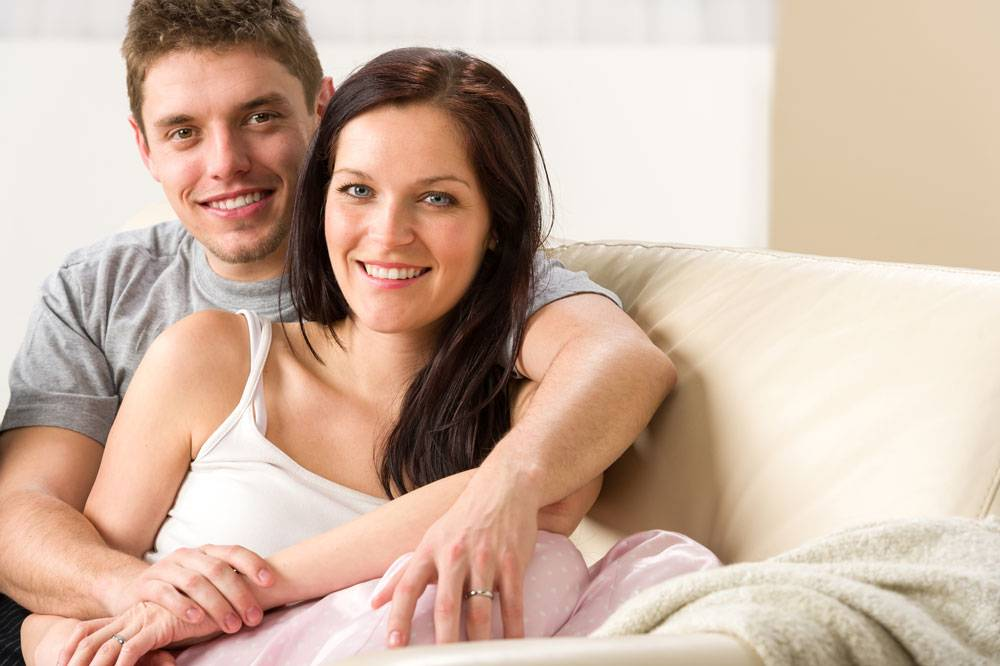Carefree young couple embracing on couch.