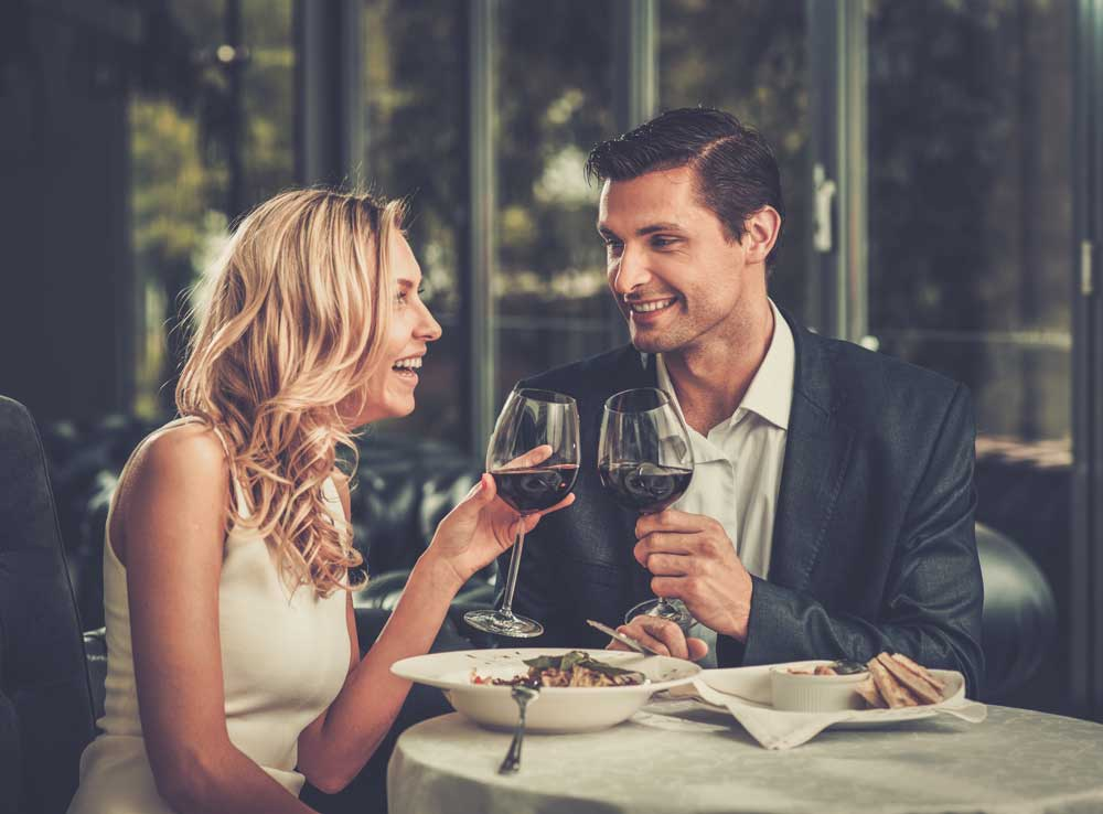 Happy couple in a restaurant with glasses of red wine.
